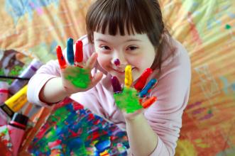 Kind mit Trisomie 21 zeigt ihre farbverschmierten Hände