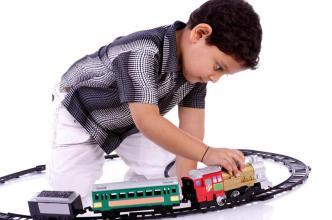 kleiner Junge spielt mit Eisenbahn
